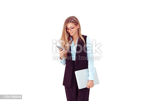 1150572102istockphoto Good business news. Happy woman girl, female in eyeglasses using phone and holding laptop in other hand. Isolated light purple white background. Positive face expression 1204185649