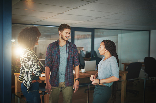 Shot of colleagues talking in a modern office