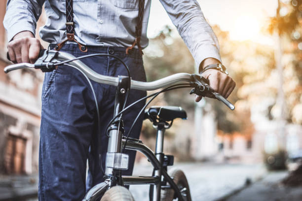 Good day for a ride on my bicycle. Cropped shot of man in smart casual wear rolling his bicycle. suspenders stock pictures, royalty-free photos & images
