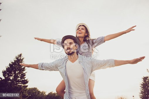 istock Good day, happiness, friendship, stroll, holiday concept. Cute sweet partner piggybacking his lady, she rides him, they are well dressed, excited, lovely, with spread hands 924023132