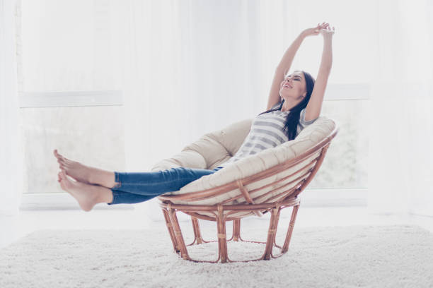 Good day! Happy cute pretty woman lying in the armchair on the weekend and stretching - foto stock