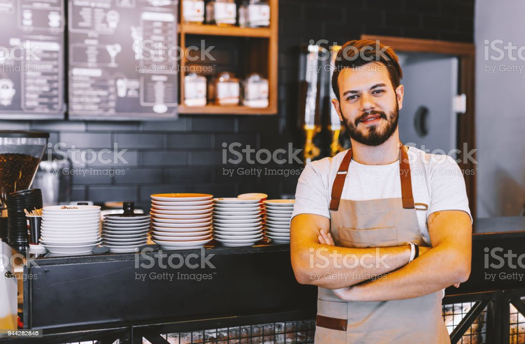 Good day start with coffee! Portrait of smiling young confident waiter handsone hipster barista man look at camera posing wearing apron standing behind the counter of a store with his arms folded in his coffee shop. xxxl size 20-29 Years Stock Photo