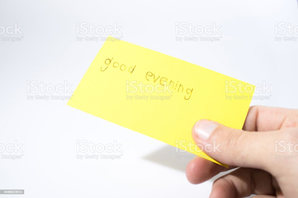 Good evening handwrite with a hand on a yellow paper compsoition stock photo