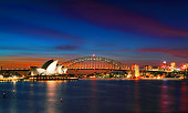 Sydney, Australia - April 8, 2014; Two of Sydney's famous icons, the Sydney Opera House and Sydney Harbour Bridge lit up at dusk after watching a magnificent sunset, the evening  sky still aglow with some colour.