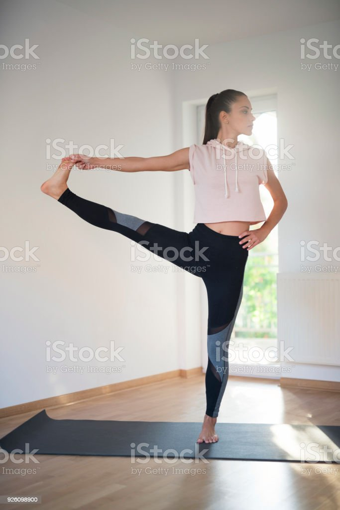 Beautiful young woman practicing yoga at home, performing extended...