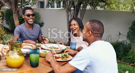 Shot of a happy family having lunch out in the backyard