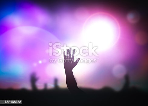 Human raised hands over blurred concert background