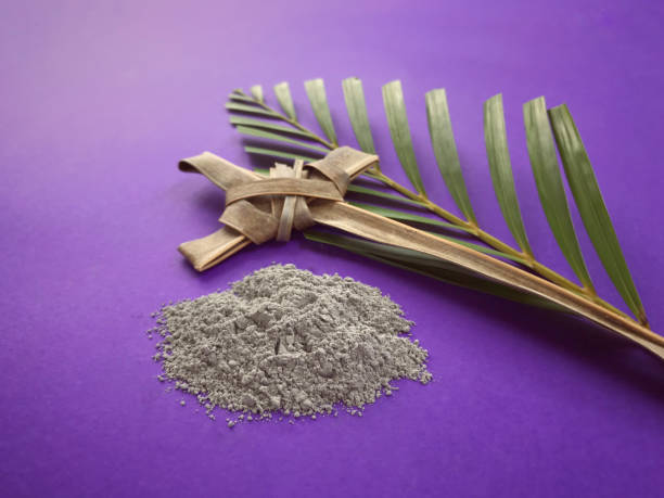 Good Friday, Lent Season, Ash Wednesday and Holy Week concept. A Christian cross, ashes and a palm leaf on purple background. lent stock pictures, royalty-free photos & images