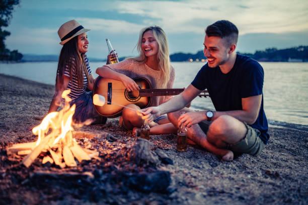 good friends and summer nights - falò spiaggia foto e immagini stock