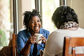 Attractive African American women have a good time with a close friend drinking good coffee.