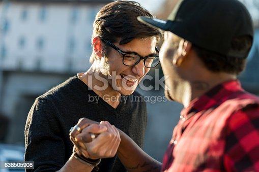 istock good friends joking about their secret handshake 638505908