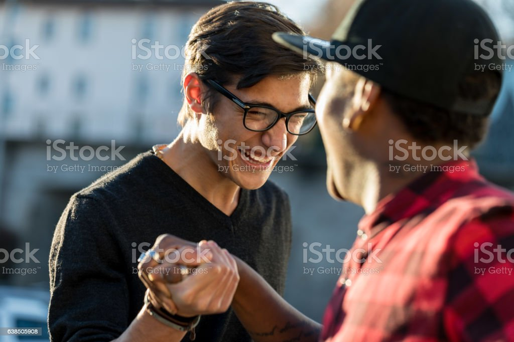 good friends joking about their secret handshake stock photo