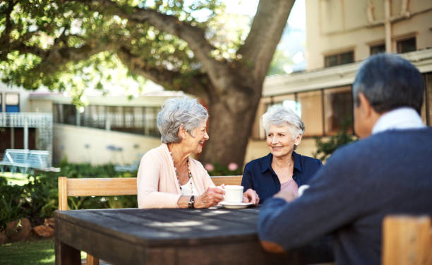 Good friends keep the happy times going Shot of a group of seniors having tea out in the garden of a retirement home retirement community stock pictures, royalty-free photos & images