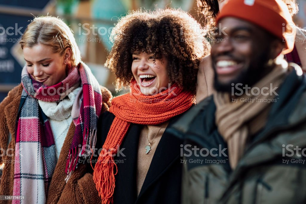 Good Friends Laughing A mixed-race woman smiles and laughs and makes good memories with close friends whilst spending the day in the city visiting the Xmas Market in Newcastle upon Tyne. 20-29 Years Stock Photo