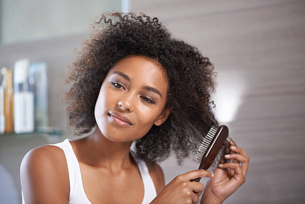 Good haircare is my number one priority Shot of an attractive young woman taking care of her hair hairbrush stock pictures, royalty-free photos & images