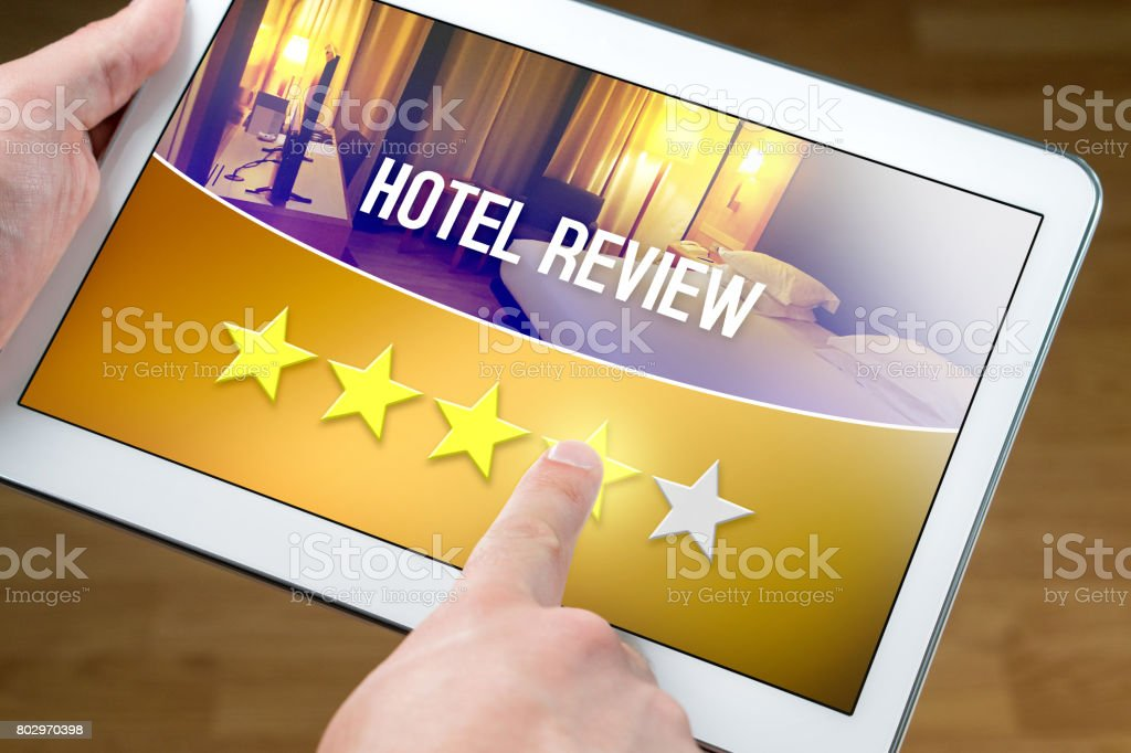 Good hotel review. Satisfied and happy customer giving great rating with tablet on an imaginary criticism site, application or website. Four out of five stars to accommodation or lodging. stock photo