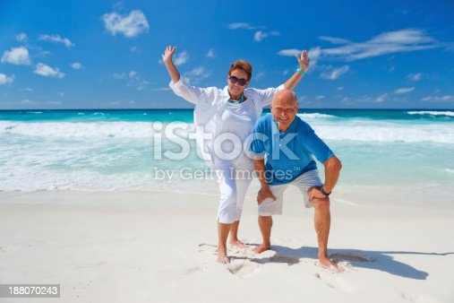 good humored best ager couple during summer vacation on sandy beach