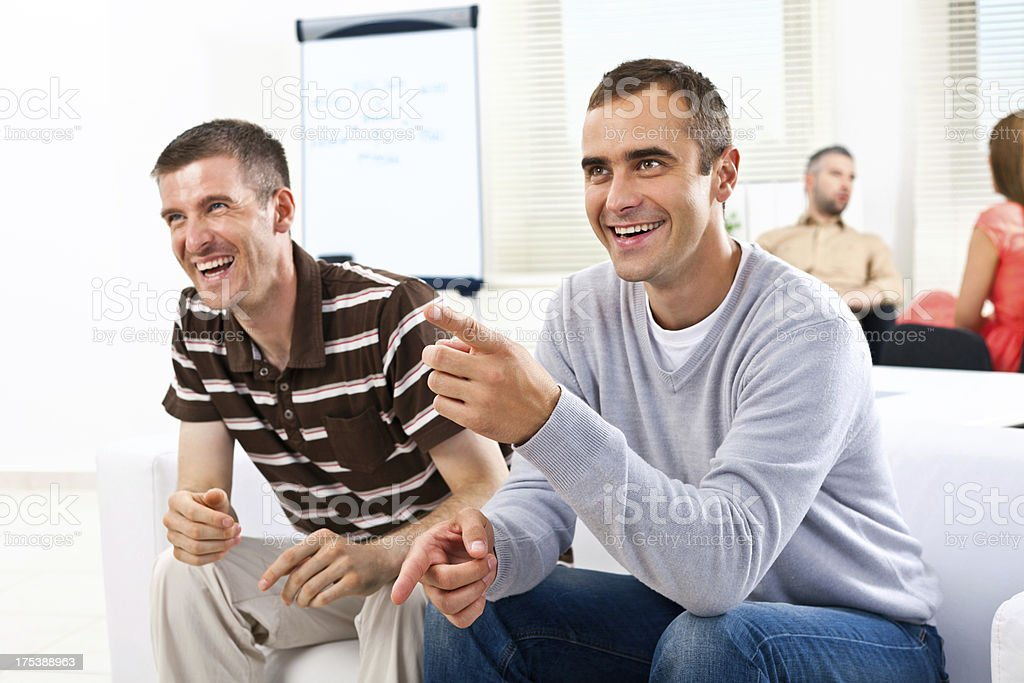 Good idea! Creative agency. Two happy business colleagues sitting on the sofa and laughing. 30-34 Years Stock Photo
