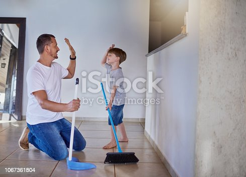 Shot of a father and his little son high fiving each other while sweeping the floor at home