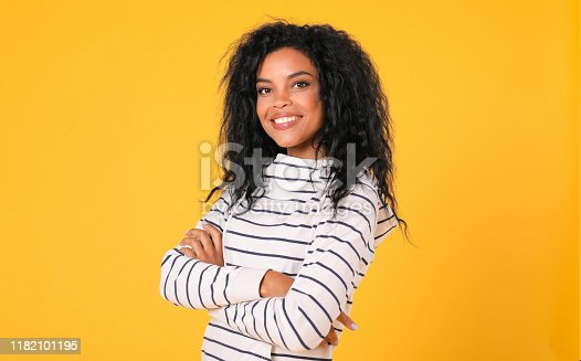 857924506 istock photo A good listener. Determined African American woman is posing on a yellow background with her hands folded, wearing a striped hoodie and looking at the camera with joy. 1182101195