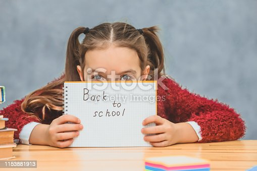 istock A good little schoolgirl is sad. Conducting paper with a text inscription back to school. Writing sitting at the school desk. Isolated on a gray background. Closing his face with a notebook, the girl looks into the camera. 1153881913