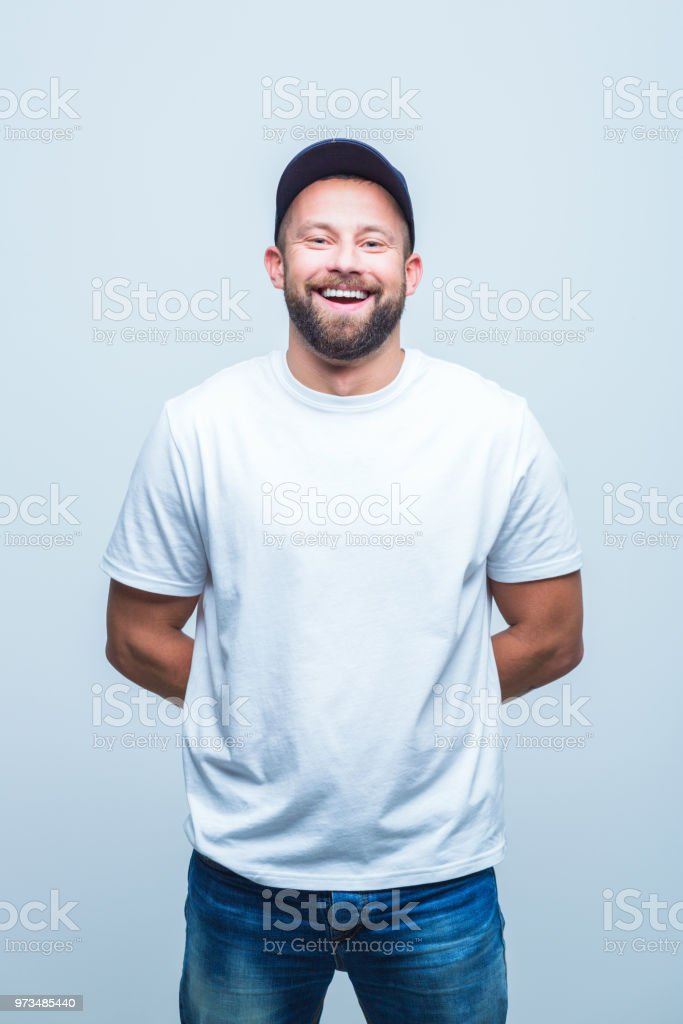 Good looking beard man laughing Portrait of good looking beard man laughing with hands behind his back on white background. Adult Stock Photo