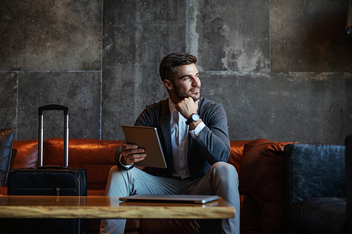 Good looking businessman sitting on a hotel couch and holding the tablet. Next to him is a suitcase. He is wearing an elegant blazer, white shirt, grey pants, and an expensive watch.Business trip