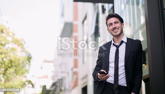 580112984 istock photo Good looking businessman walking through the city 844552248