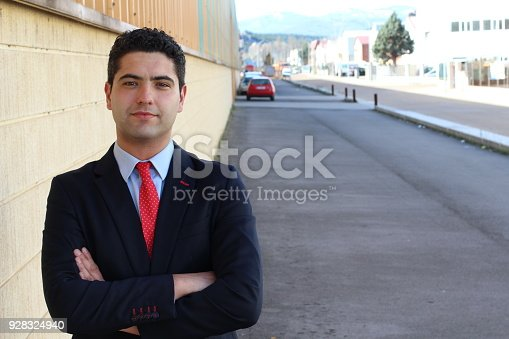 580112984 istock photo Good looking businessman with arms crossed outdoors 928324940