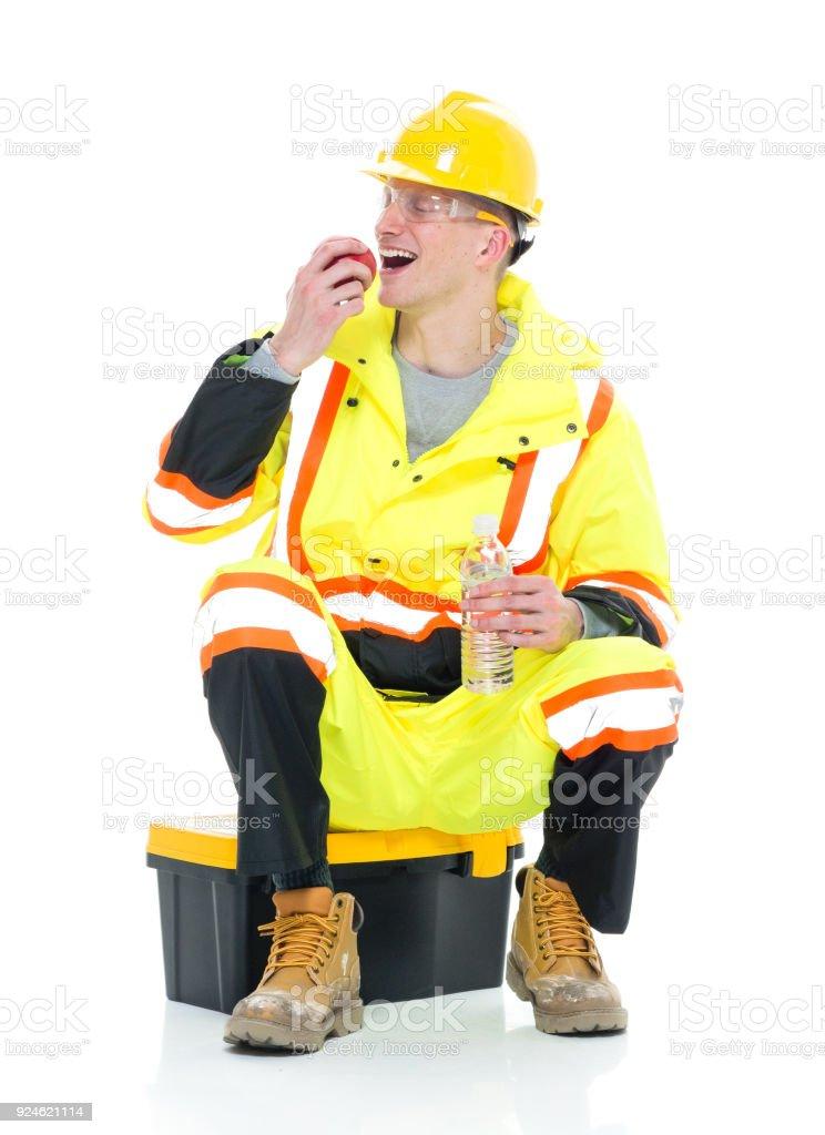 Gut aussehend Bauarbeiter hält Apfel und Wasser boottle – Foto