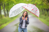 istock Good looking female holds two umbrellas above her in the rain during a walk in the nature. 1240302386