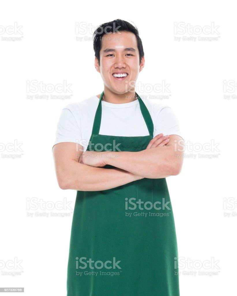 Good looking Korean American male wearing a green apron stock photo