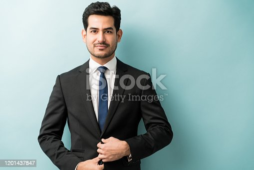 Young male entrepreneur making eye contact against blue background