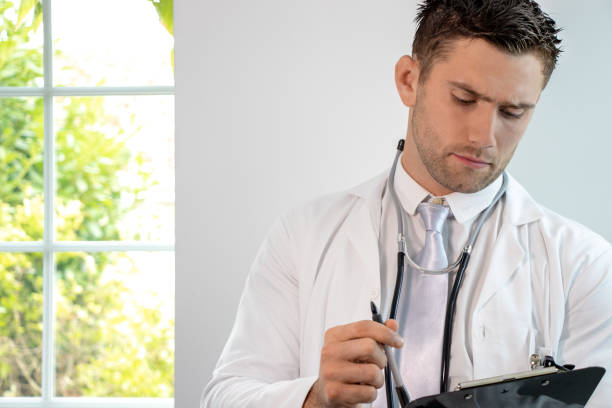 Good looking male doctor, gp, with stethoscope and clipboard stock photo