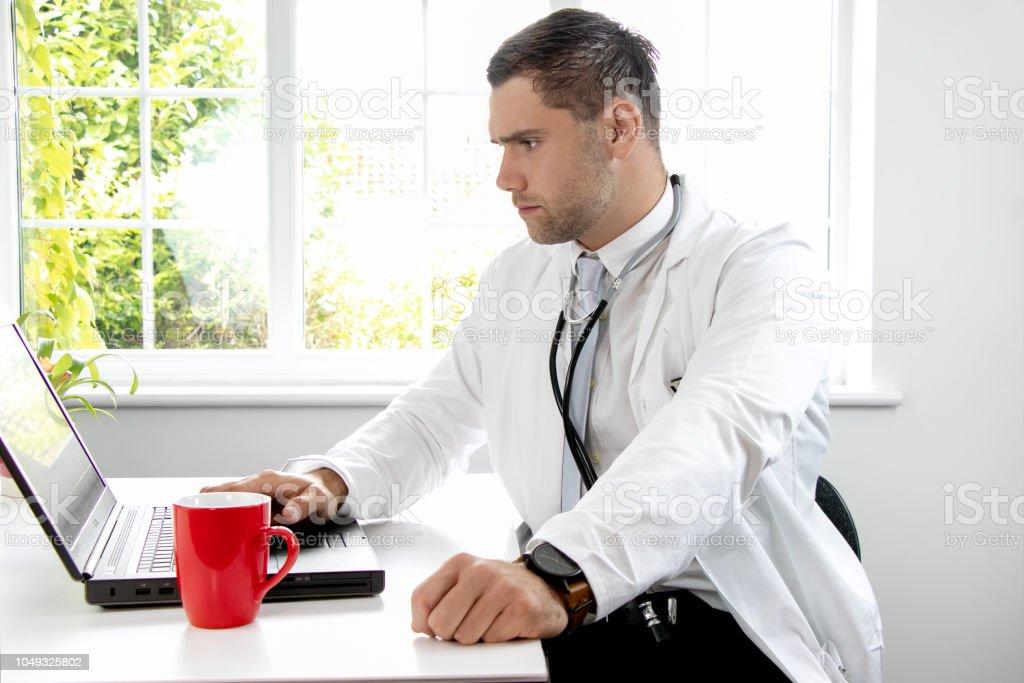 Gut Aussehenden Mannlichen Arzt Weiss Labor Mantel Gp In Blick Auf Laptopcomputer Schreibtisch Stockfoto Und Mehr Bilder Von Arzt Istock
