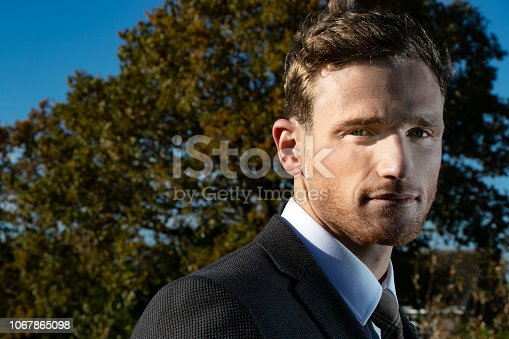 471947536 istock photo Good looking man dressed in a suit in countryside with trees and and blue sky in background 1067865098