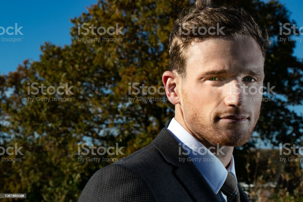 Good looking man dressed in a suit in countryside with trees and and blue sky in background stock photo