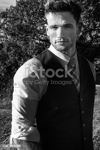 471947536 istock photo Good looking man dressed in a suit in countryside with trees and fields behind behind him 1067862096