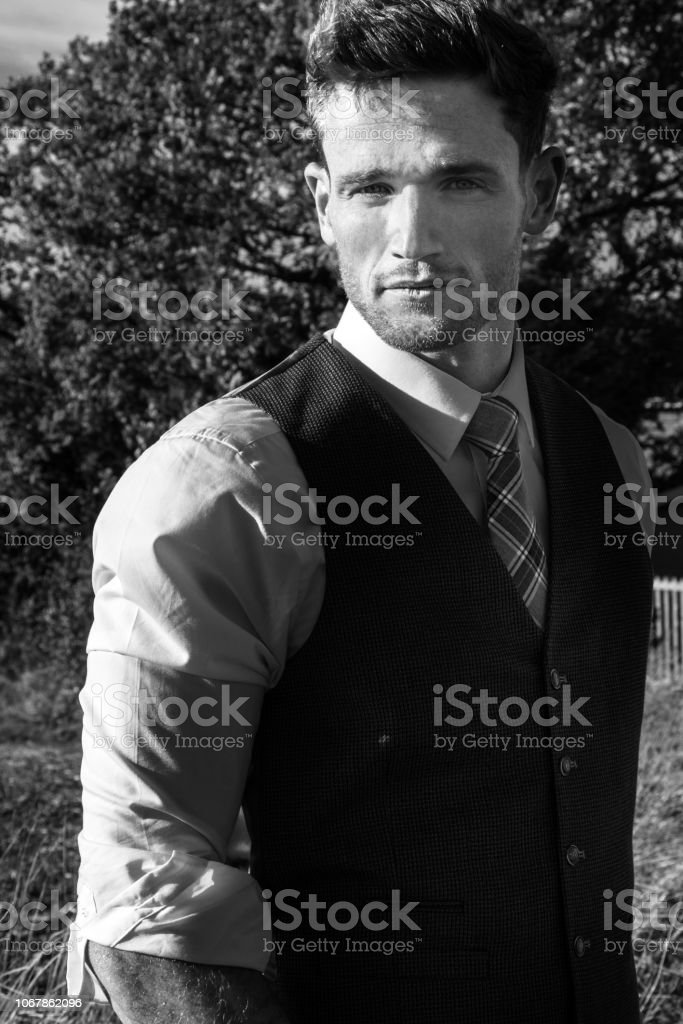 Good looking man dressed in a suit in countryside with trees and fields behind behind him stock photo