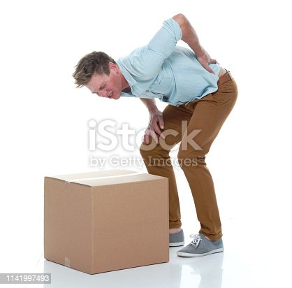 Good looking man holding a brown box and has back pain