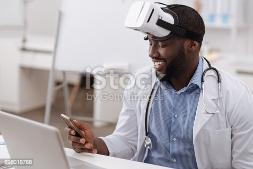 istock Good looking positive scientist holding a cell phone 698016768