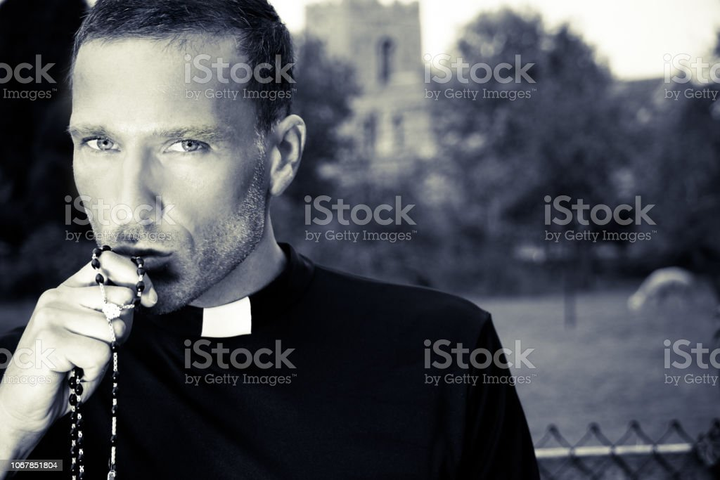 Good looking priest kisses his rosary with church, field and alpaca in background stock photo