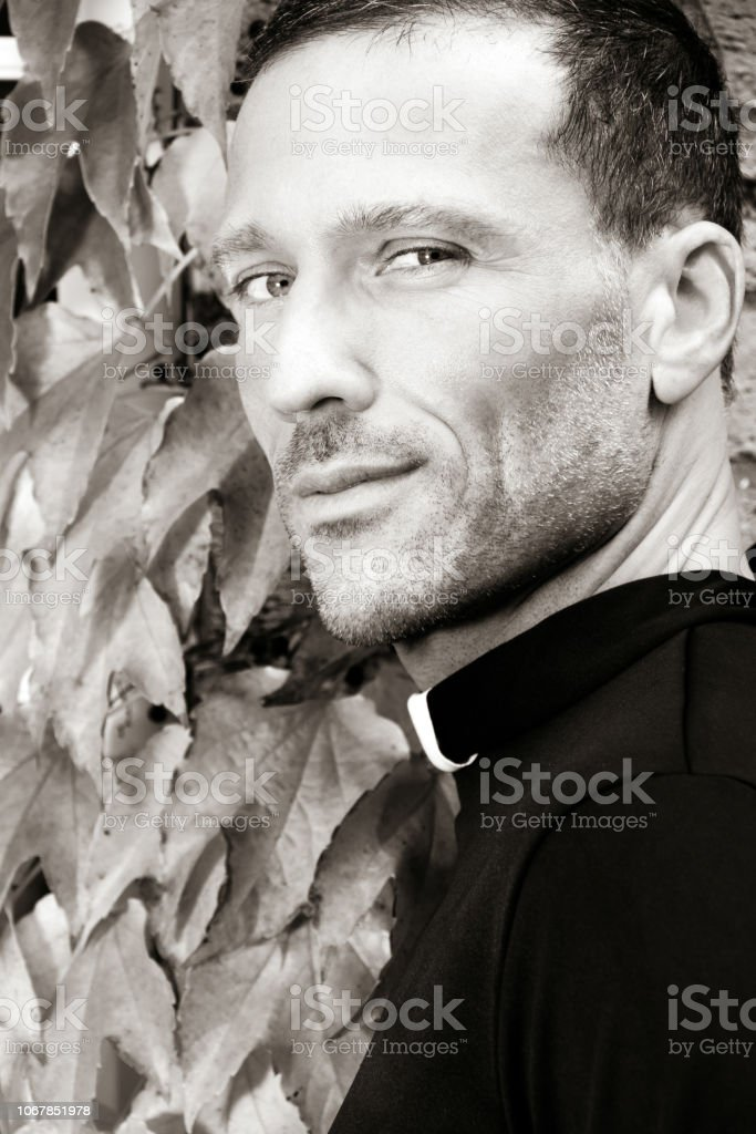 Good looking priest looks over his shoulder to camera with ivy in the background stock photo
