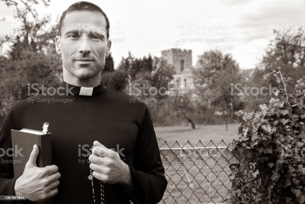 Good looking priest stands in front of fence to field with church in background stock photo