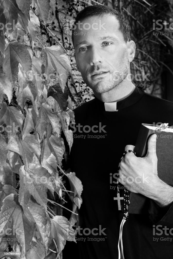 Good looking priest stands in garden holding his bible next to virginia creeper ivy stock photo