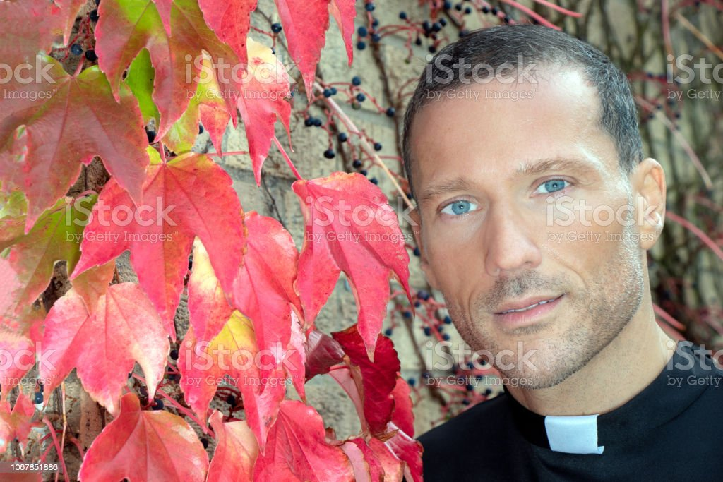 Good looking priest with visible collar poses for portrait next to red virginia creeper ivy stock photo