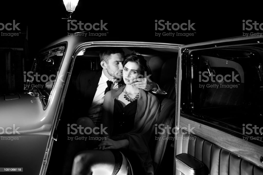 Good looking sexy couple, handsome man in suit, beatiful woman in red dress, embrace passionately in vintage car stock photo