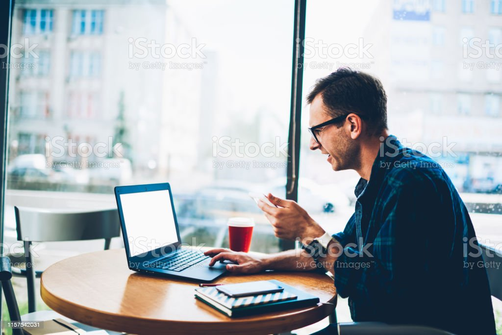 Good looking smiling professional male freelancer in trendy eyewear watching funny video in popular webpage using laptop computer with blank screen connected to 4G internet while sitting indoors - Royalty-free Adult Stock Photo