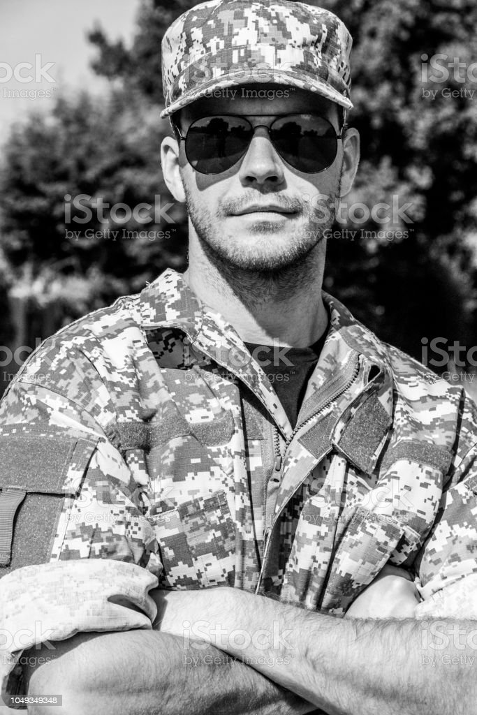 Good looking soldier in uniform standing with arms crossed looking at camera stock photo