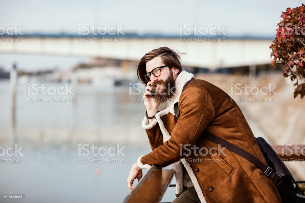 Good looking unshaven man leaned on the fence talking on the phone. stock photo